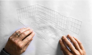 A man is using both of his hands to feel the raised lines of an architectural drawing.