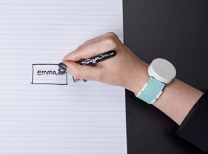 A woman wearing watch-like device, The Emma, on her wrist writes the name Emma on a sheet of lined paper.