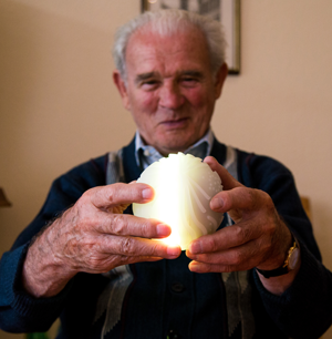 An elderly man holds an illuminated Ichó ball.