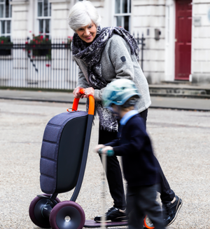 An older woman rides her Scooter for Life alongside her young grandson, who is riding a child's scooter.