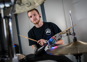 A drummer plays the drums using the Robotic Drumming Prosthesis.